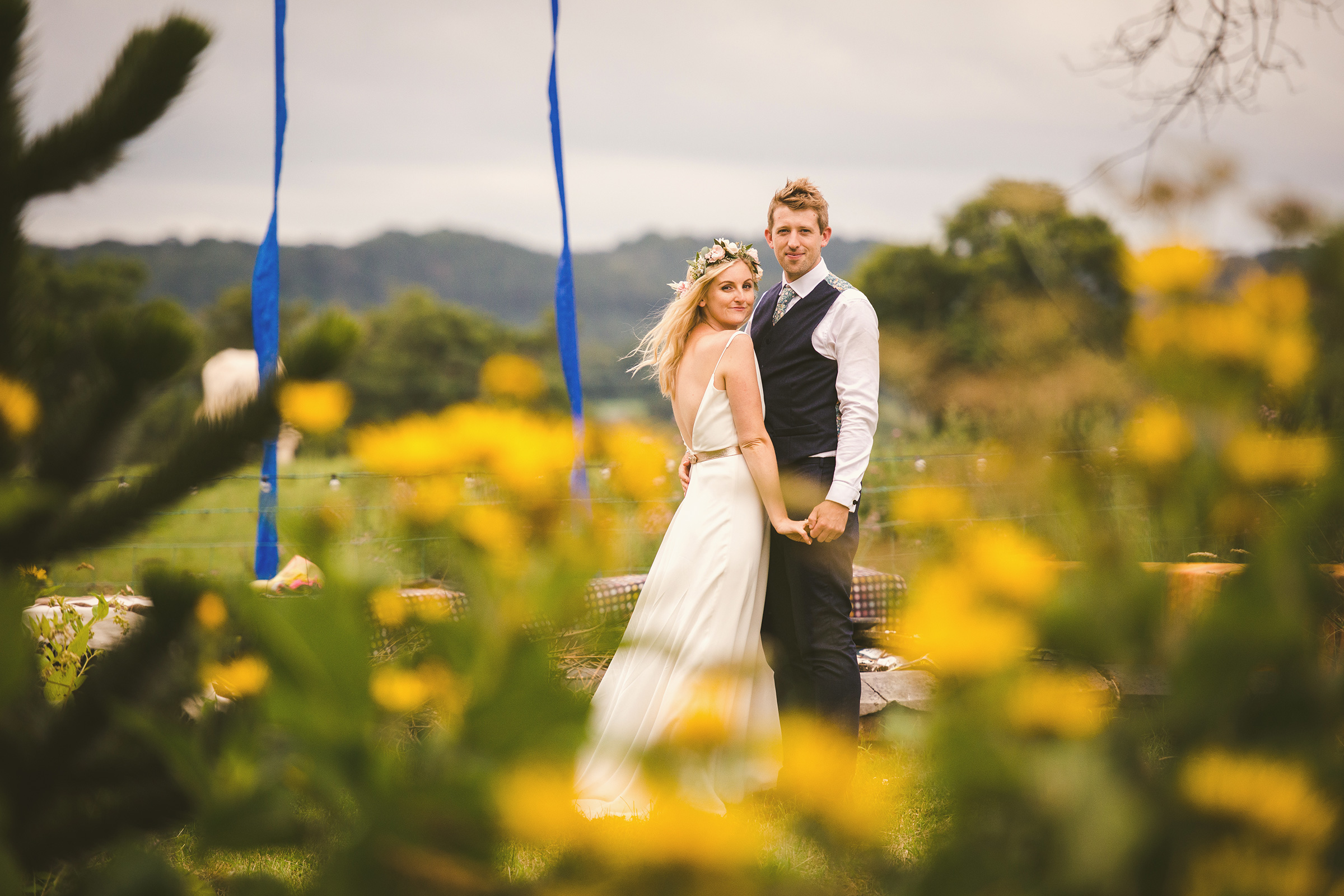 bride and groom in couple pose in garden with yellow flowers